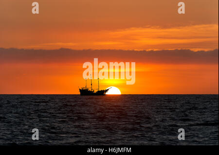 Pirate ship ocean sunset silhouette is an old wooden pirate ship with full flags as the sun sets on the ocean horizon - Stockfoto