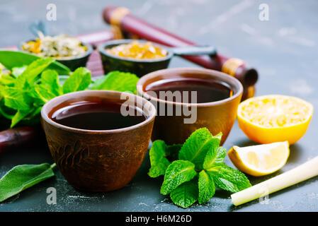 frischer Tee in Tassen und auf einem Tisch - Stockfoto