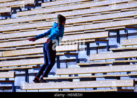 Training. Young woman jumping on stadium stairs. - Stock Photo