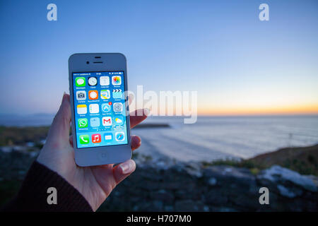 Hands using a smart phone to take a photograph of a landscape at twilight - Stock Photo