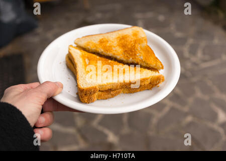 First person perspective of grilled cheese sandwich cut in half diagonally and set in a foam plate - Stockfoto
