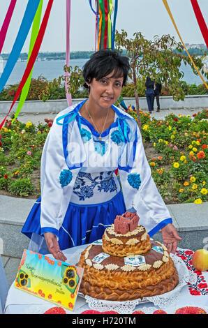 Dnepropetrovsk, Ukraine - September 14, 2013: Ukrainian women in national costumes show home cooking and folk art - Stock Photo