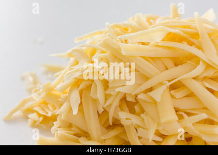 Grated yellow hard cheese on white - Stock Photo
