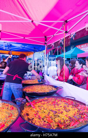 LONDON, UNITED KINGDOM - SEPTEMBER 11TH 2016: A Spanish guy serves authentic paella to a customer at Portobello - Stock Photo