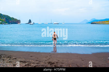 The black sand beach with yachts in small haven and young man, going to swim, in Porto di Ponente - Stock Photo