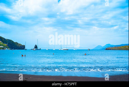 The black sand beach with yachts in small haven and swimming tourists, in Porto di Ponente, - Stock Photo