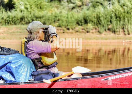 Elderly Woman looks through binoculars while canoeing on the Green River in Canyonlands National Park, Utah - Stock Photo