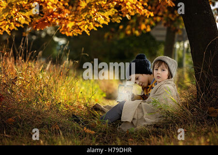 Two children, boys, hugging under blanket, sitting under a tree on a sunny autumn afternoon, holding lantern, beautiful - Stock Photo