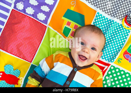 Baby boy playing on a play mat - Stock Photo