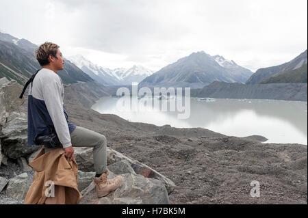 A man at Tasman Glacier viewpoint, Aoraki / Mount Cook National Park, New Zealand - Stock Photo