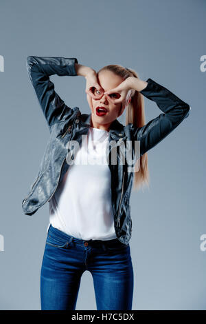 Fashion model pulling her hair in tail and looking at camera - Stock Photo