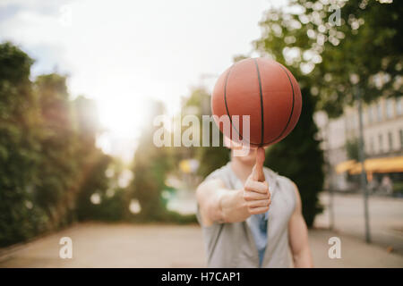 Man balancing basketball on his thumb on outdoor court. Streetball player spinning the ball. Focus on basketball. - Stock Photo