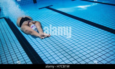 Underwater shot of woman training in swimming pool after dipping. Female swimmer in action inside swimming pool. - Stockfoto