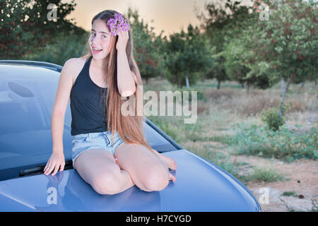 A 13 year old teenage girl with braces on her teeth sitting on a car with flowers in her long hair enjoying the - Stock Photo