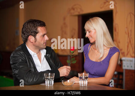 Date, man and woman with a red rose at the bar - Stockfoto
