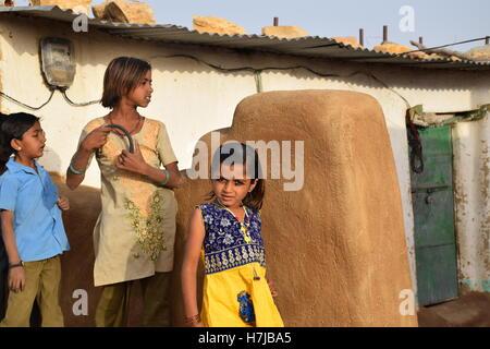Indian kids in a village inside Thar desert near Jaisalmer, Rajasthan, India - Stock Photo