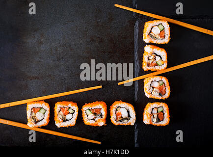 Traditional Japanese food - sushi, rolls and chopsticks for sushi on a dark background. Top view - Stock Photo