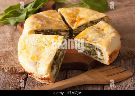 Tasty sliced Greek spanakopita pie close-up on the table. horizontal - Stock Photo