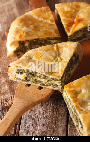 The cut pie spanakopita close-up on the table. vertical - Stock Photo