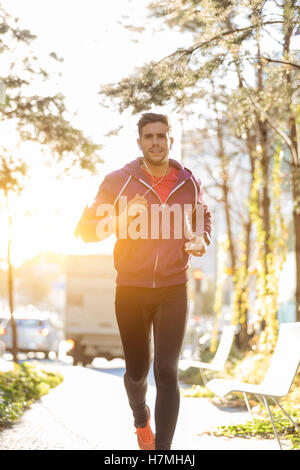 athlete with earphones running in the city - Stockfoto
