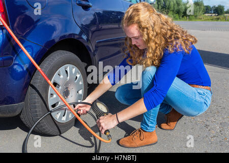 Female driver checking air pressure of car tire outdoors - Stock Photo