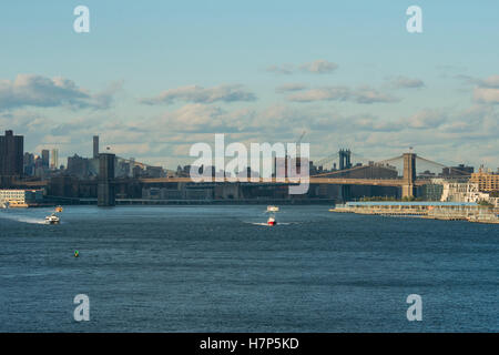 Brooklyn New York seen across the harbour from the deck of an ocean liner, a red boat passing under - Stock Photo