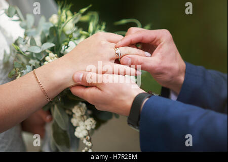 groom hand putting a wedding ring on the bride finger - Stock Photo