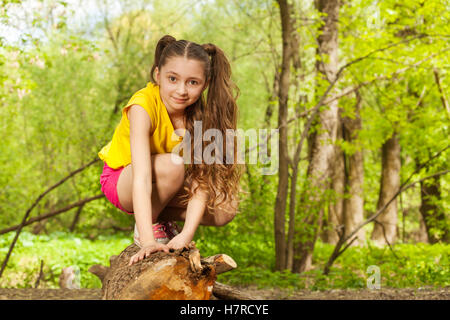 Cute young girl posing on a log in the forest - Stock Photo