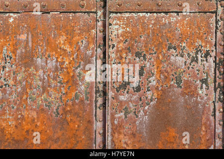 A rusty metal surface with structural joints and rivets. - Stock Photo
