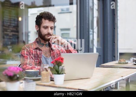 Young tattooed hipster using laptop outside cafe - Stock Photo