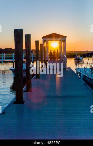 Three friends on dock at sunset; inland bay & marshes near Charleston; South Carolina; USA - Stock Photo