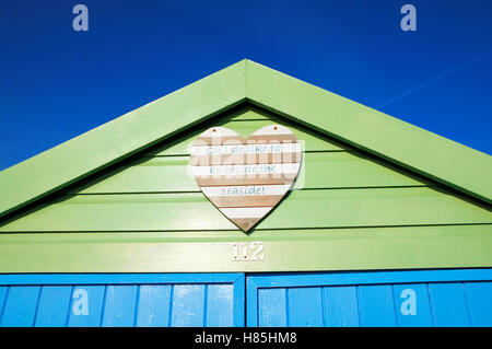 Freshly painted beach hut with a cheery wooden heart plaque displaying the lyrics 'Oh I do like to be beside the - Stock Photo