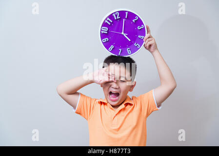 Asian boy showing and holding purple or violet clock in studio shot, on grey wall background with soft shadow - Stockfoto