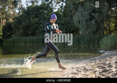Sportive girl runs on the waterfront - Stock Photo