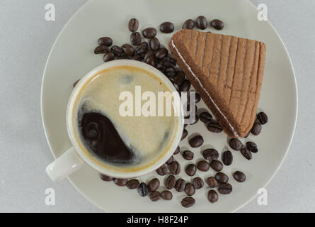A cup of coffee with slice of chocolate cake on White background - Stock Photo