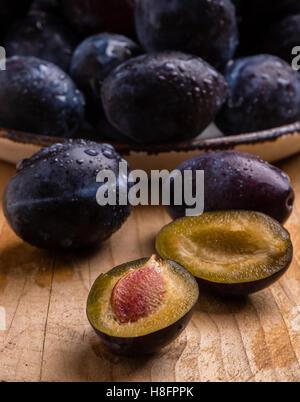 fresh organic tasty plums on wooden table - Stockfoto