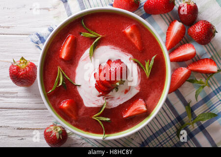 Delicious strawberry soup with cream and mint in a bowl closeup. vertical view from above - Stock Photo