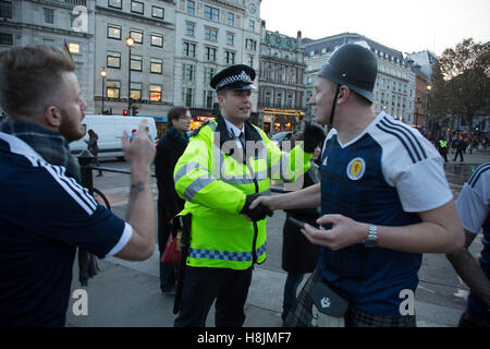Scotland fans joke with a police officer in joyous mood drinking and singing together in Trafalgar Square ahead - Stockfoto