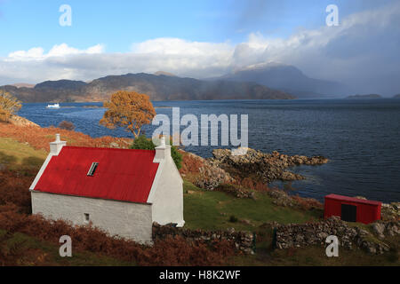 Lovely white cottage with red roof by the shores of Loch Shieldaig in Autumn on an overcast day - Stock Photo
