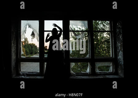 Halloween witch silhouette stand on windowsill of window frame. - Stock Photo