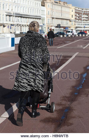 Woman in animal print coat with stroller on promenade, Beach at Hastings, UK © Linda Dawn Hammond / IndyFoto  Feb - Stock Photo