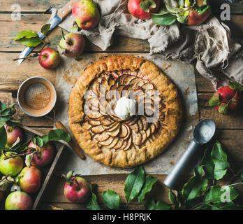 Apple crostata with cinnamon, ice-cream scoop and fresh apples - Stock Photo
