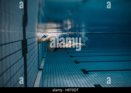 Shot of fit young woman turning over underwater. Female swimmer in action inside swimming pool. - Stockfoto