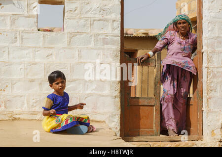 Woman and daughter in front of their house in a village near Jaisalmer, India - Stock Photo