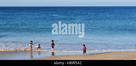 Children playing on a beach along Algoa Bay in Port Elizabeth, one of the largest cities in South Africa - Stock Photo