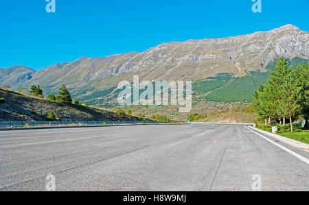 The free highway with the huge Gran Sasso rocky slopes on the distance, Abruzzo, Italy. - Stock Photo