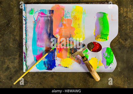Brush and brayer with paint on the floor - Stock Photo