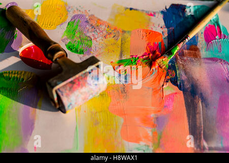 Close up of a brush and a roller with paint on a palette - Stock Photo