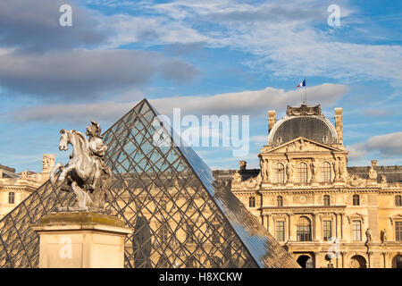 PARIS - SEPTEMBER 19, 2013: Equestrian statue of king Louis XIV in front of Louvre Palace and  the Pyramid in Paris, - Stock Photo