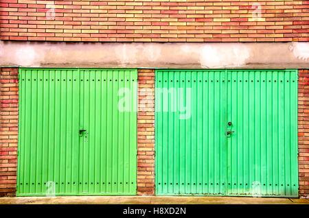 red brick garage green door - Stock Photo